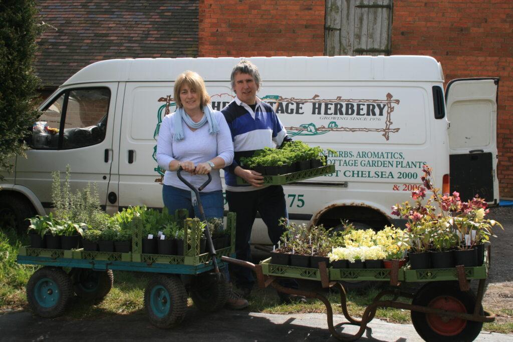 two people in front of wheelbarrows of herbs, van behind